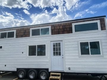 White tiny home with wood trim along top by windows