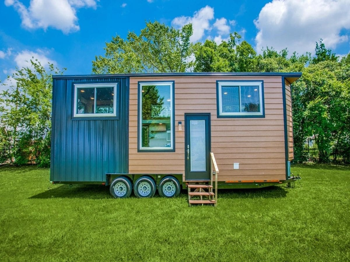 Teal and wood siding on tiny home with three large windows and door on front