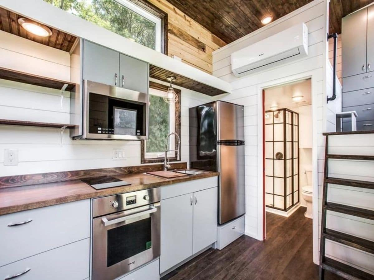 Kitchen with stainless steel full sized appliances in white counters with wood accents
