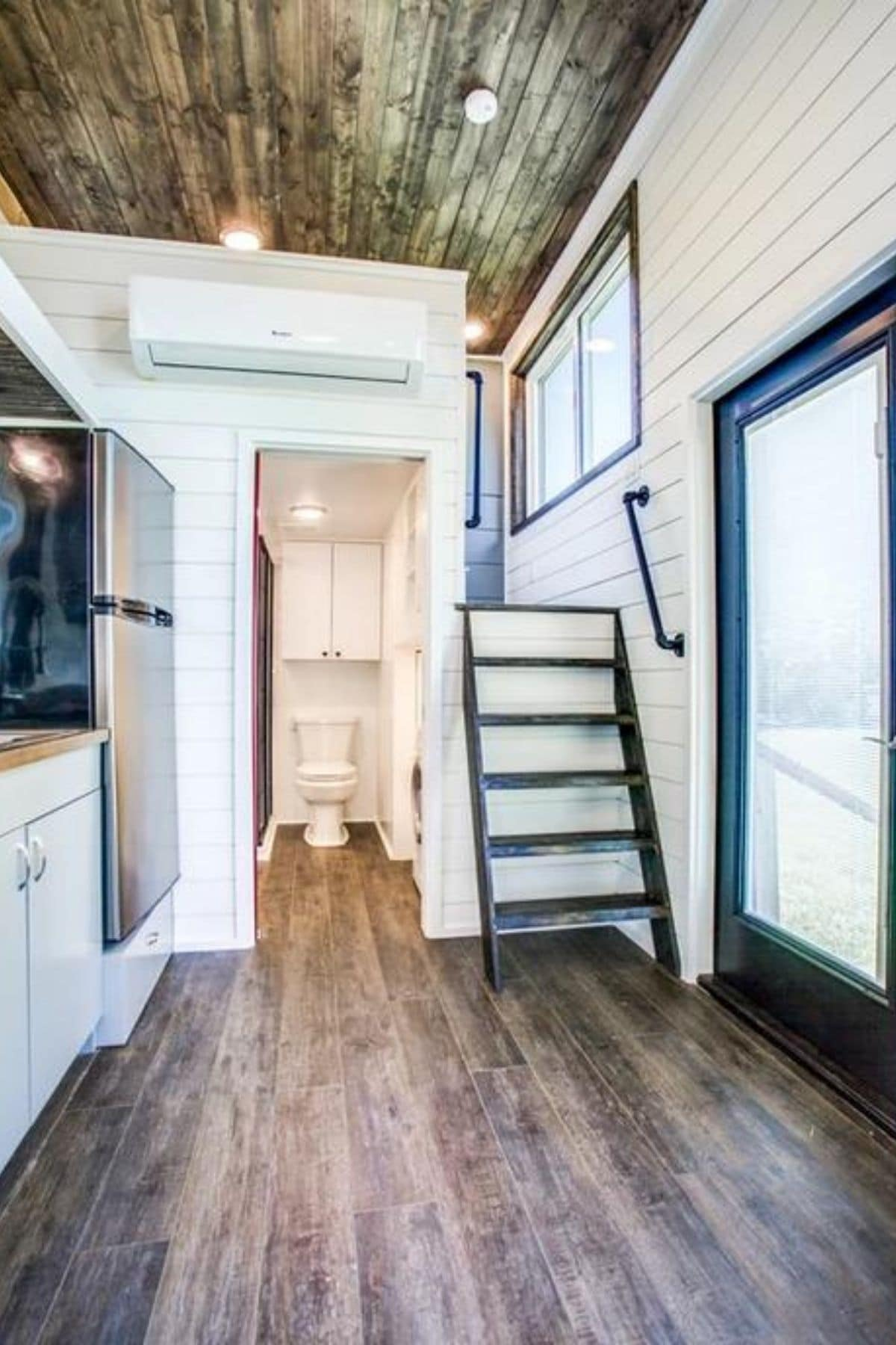Open door to bathroom with ladder to the right