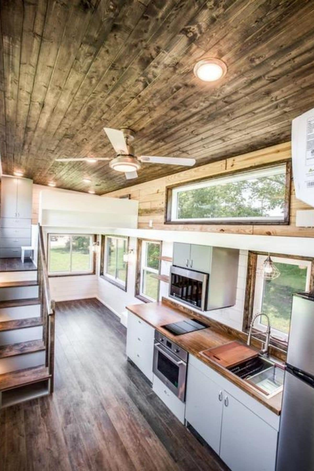 View from loft across top of tiny home showing shelving and ceiling fan
