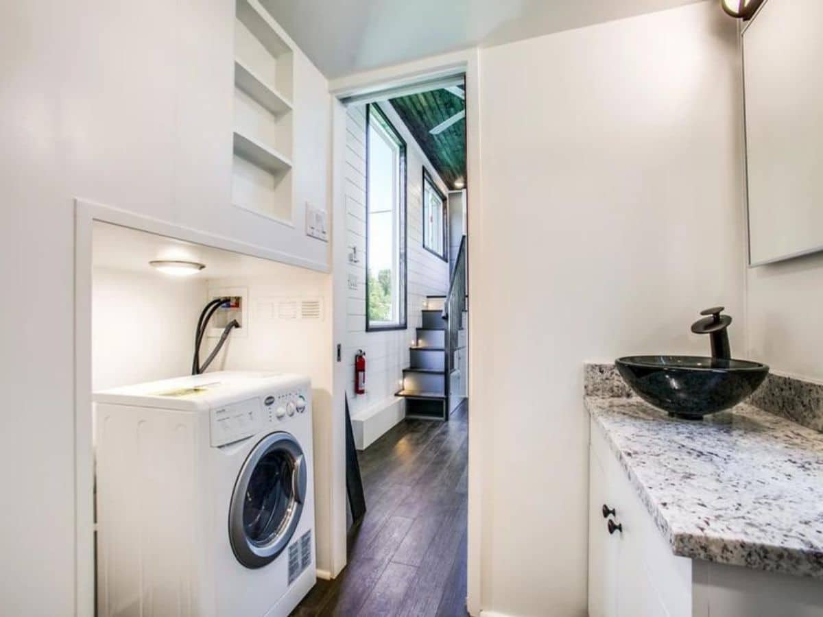 White walls and cabinets in bathroom with combination washer and dryer inside doorway