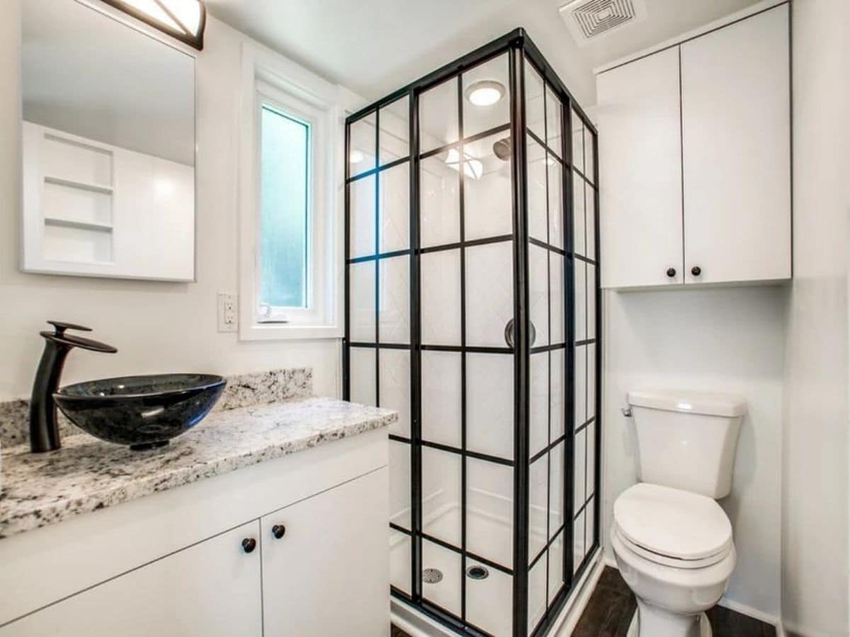 Custom black cage style shower against white bathroom walls with toilet and sink on either side