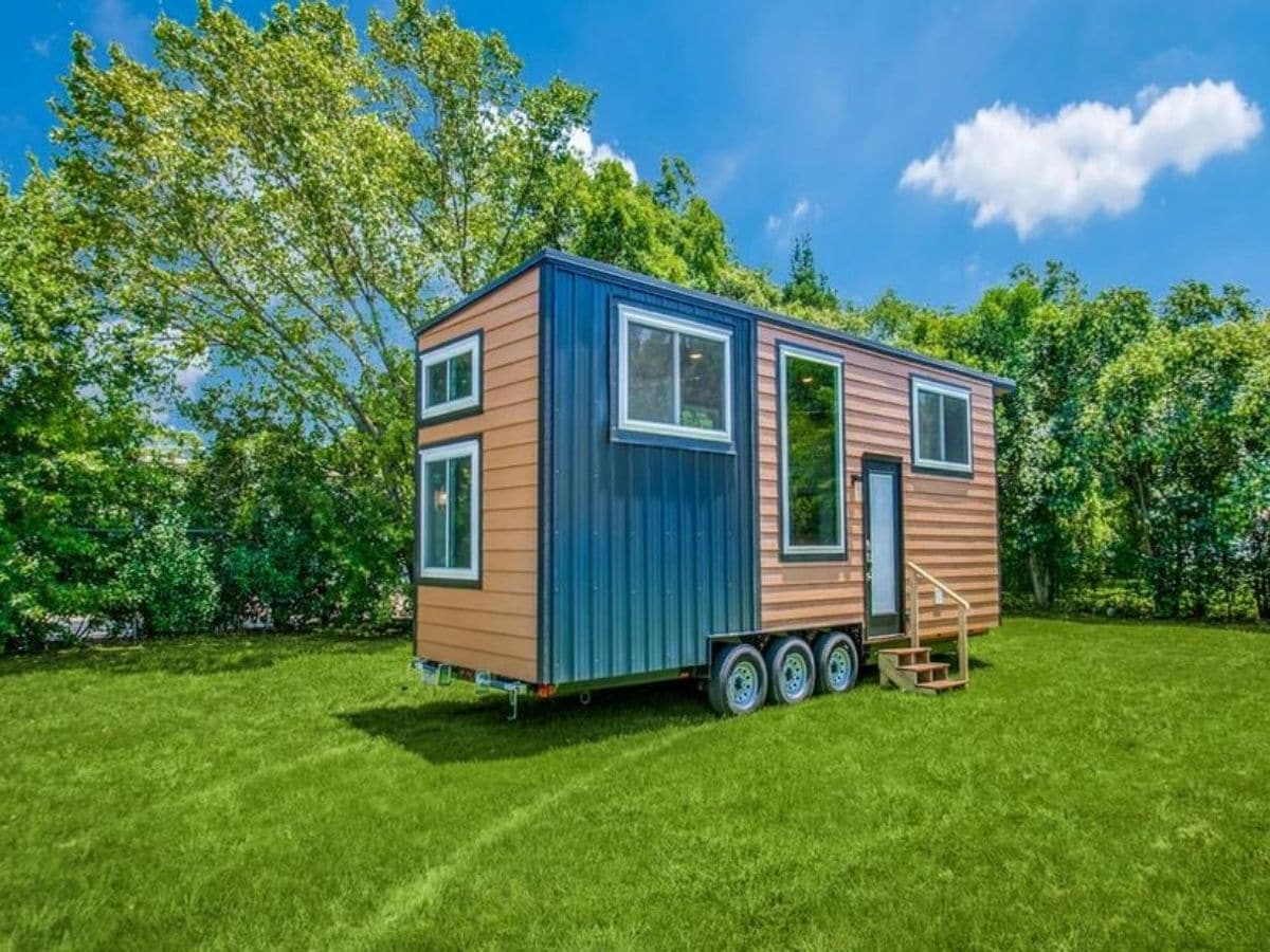 Tiny home with wood and teal siding on grass