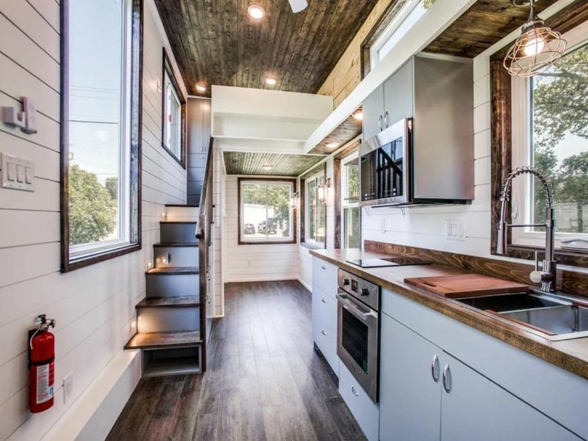 Inside tiny home with stairs on left and kitchen on right