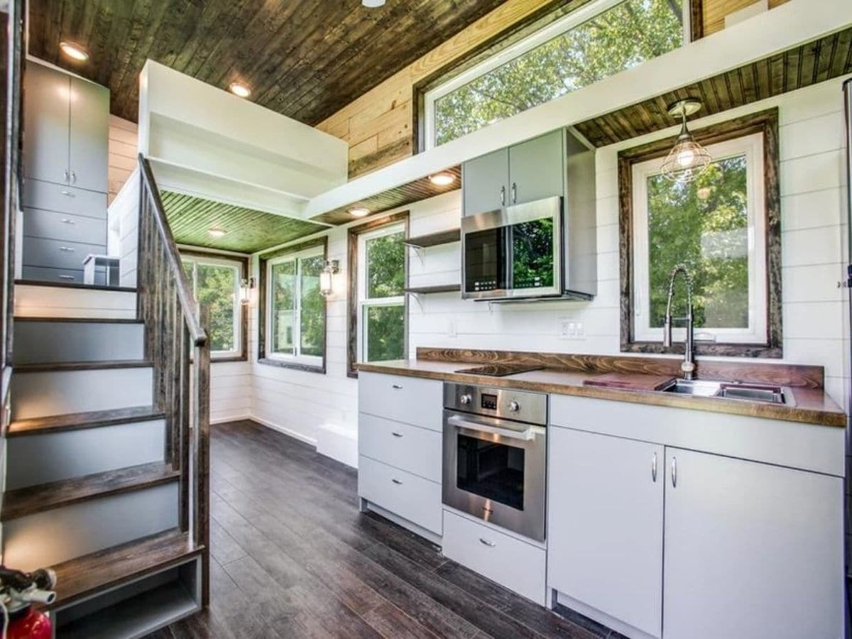 Stainless steel stove and microwave in white cabinets of tiny kitchen