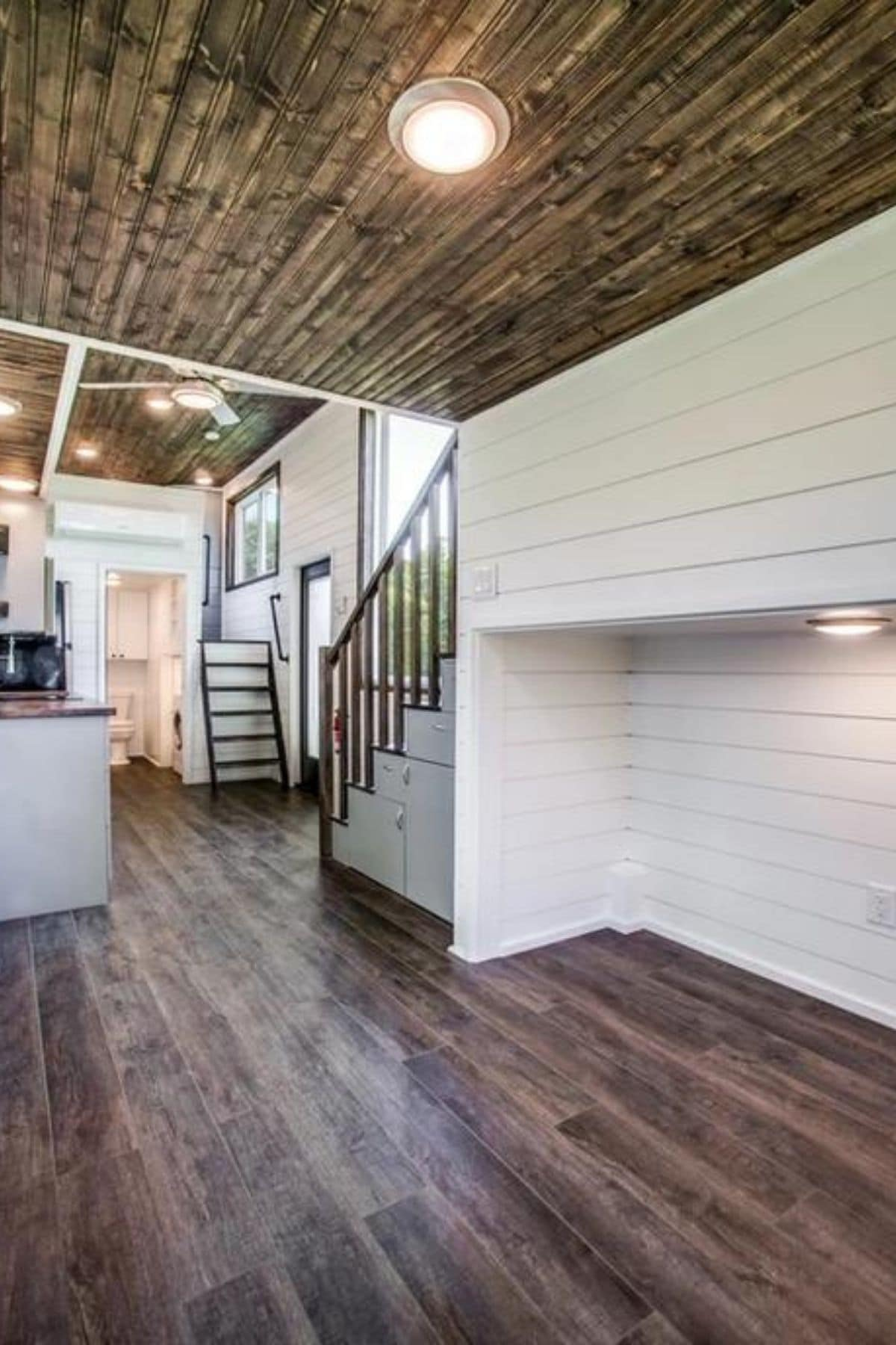Open living space behind stairs with shelf against white shiplap wall