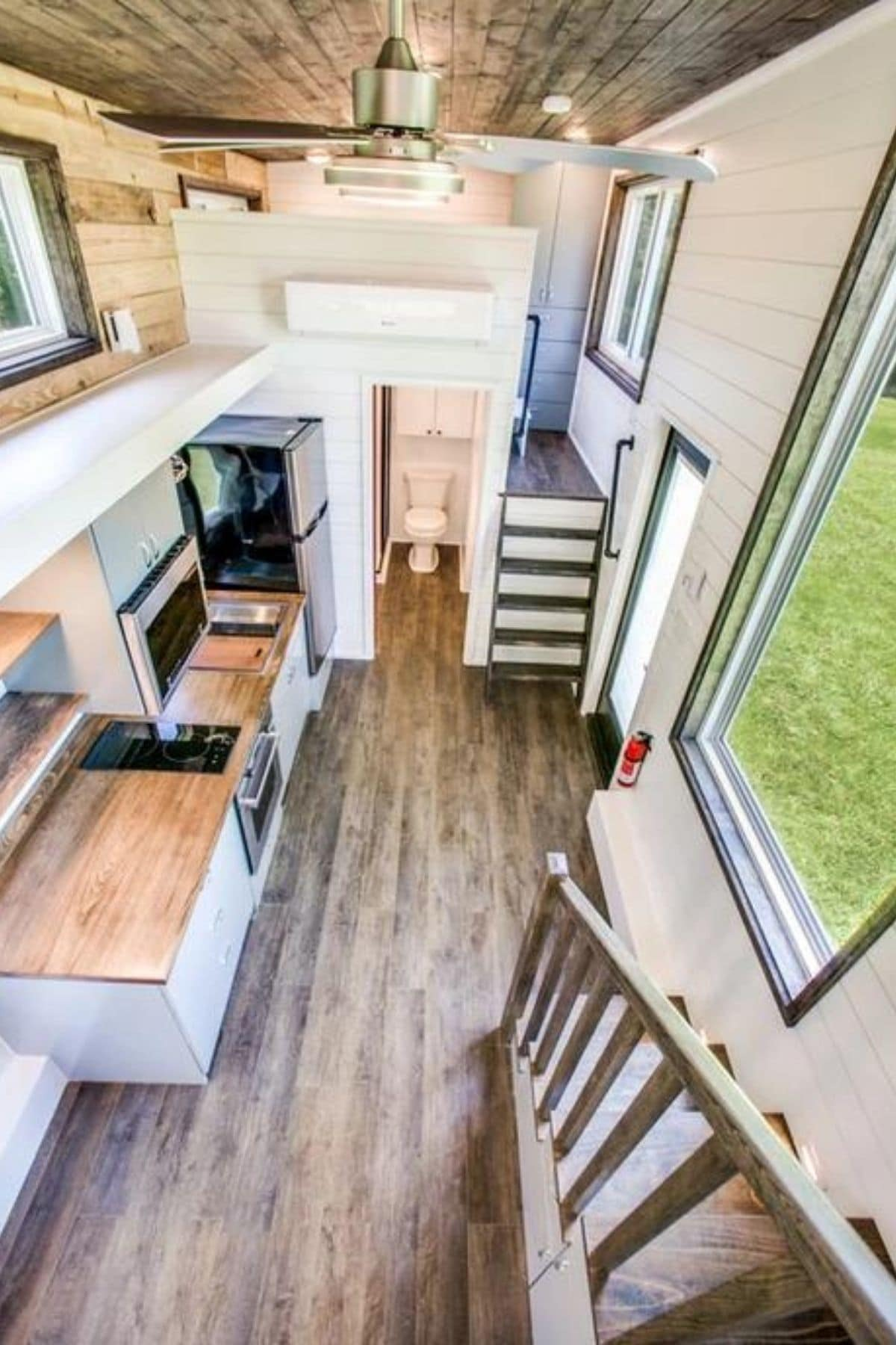 View down into tiny home from loft showing kitchen and stairs