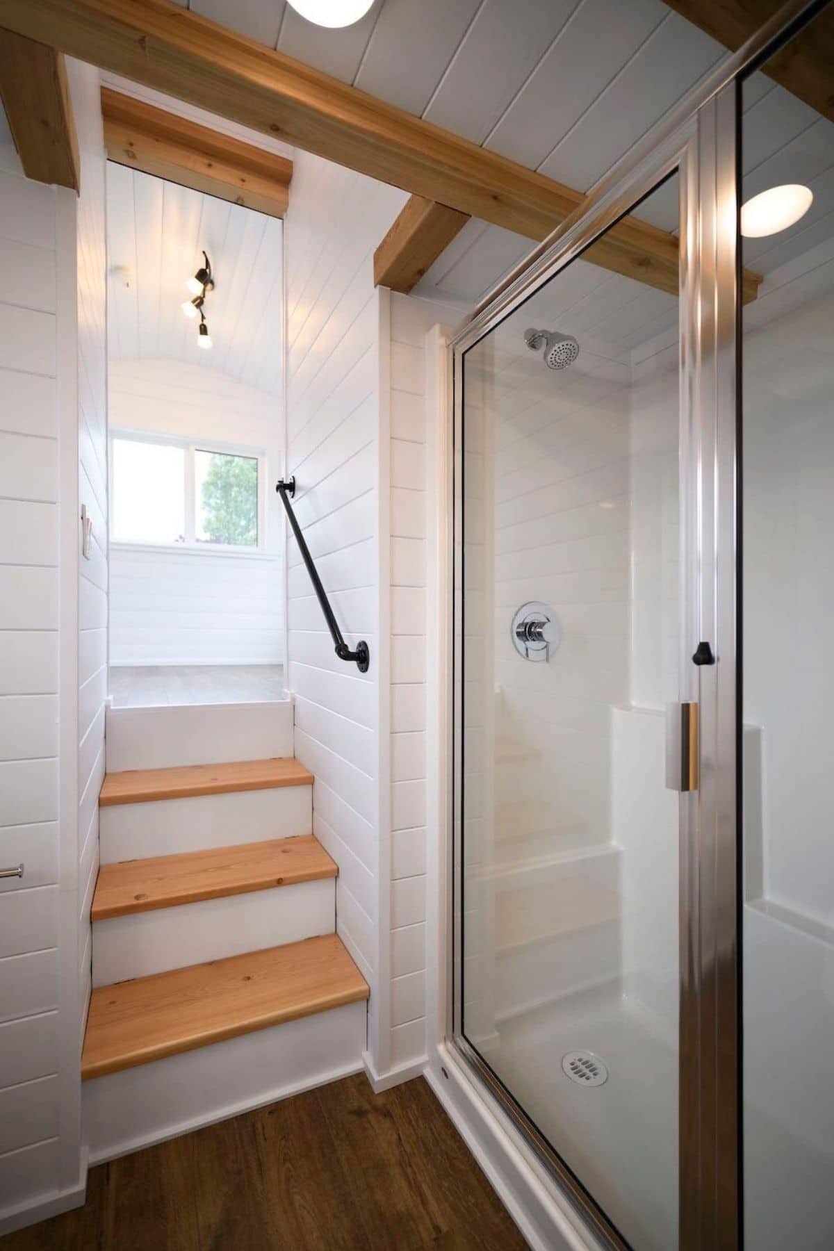Stairs up to loft next to glass door of shower