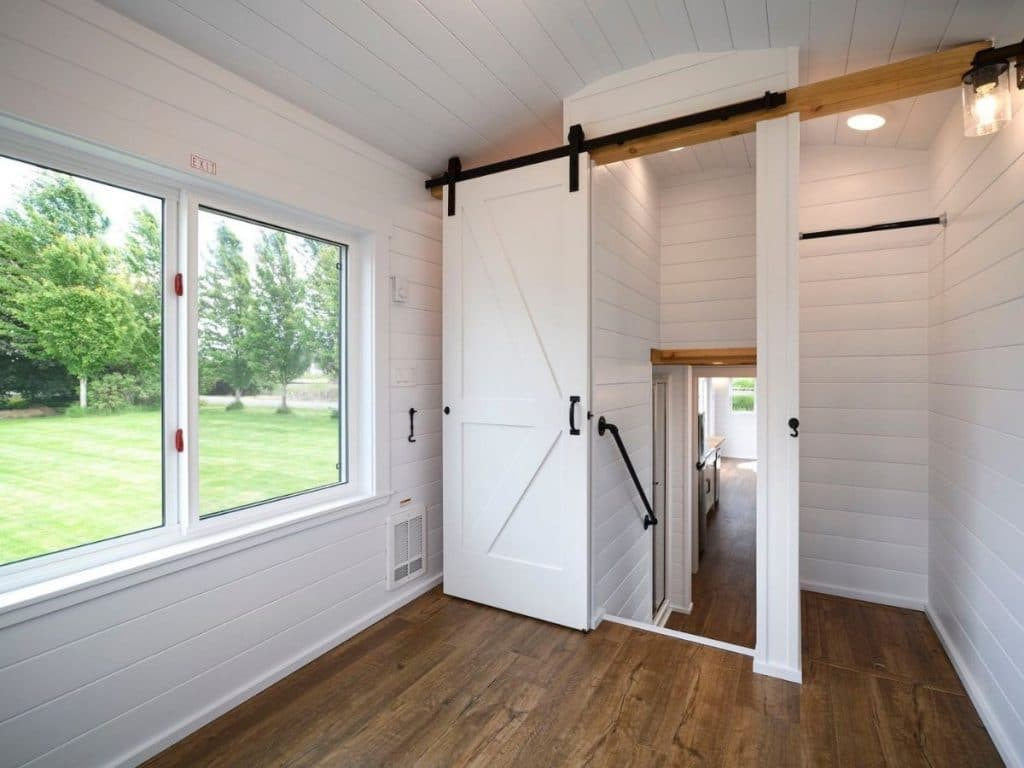 White barn door open showing steps down to main floor of tiny home