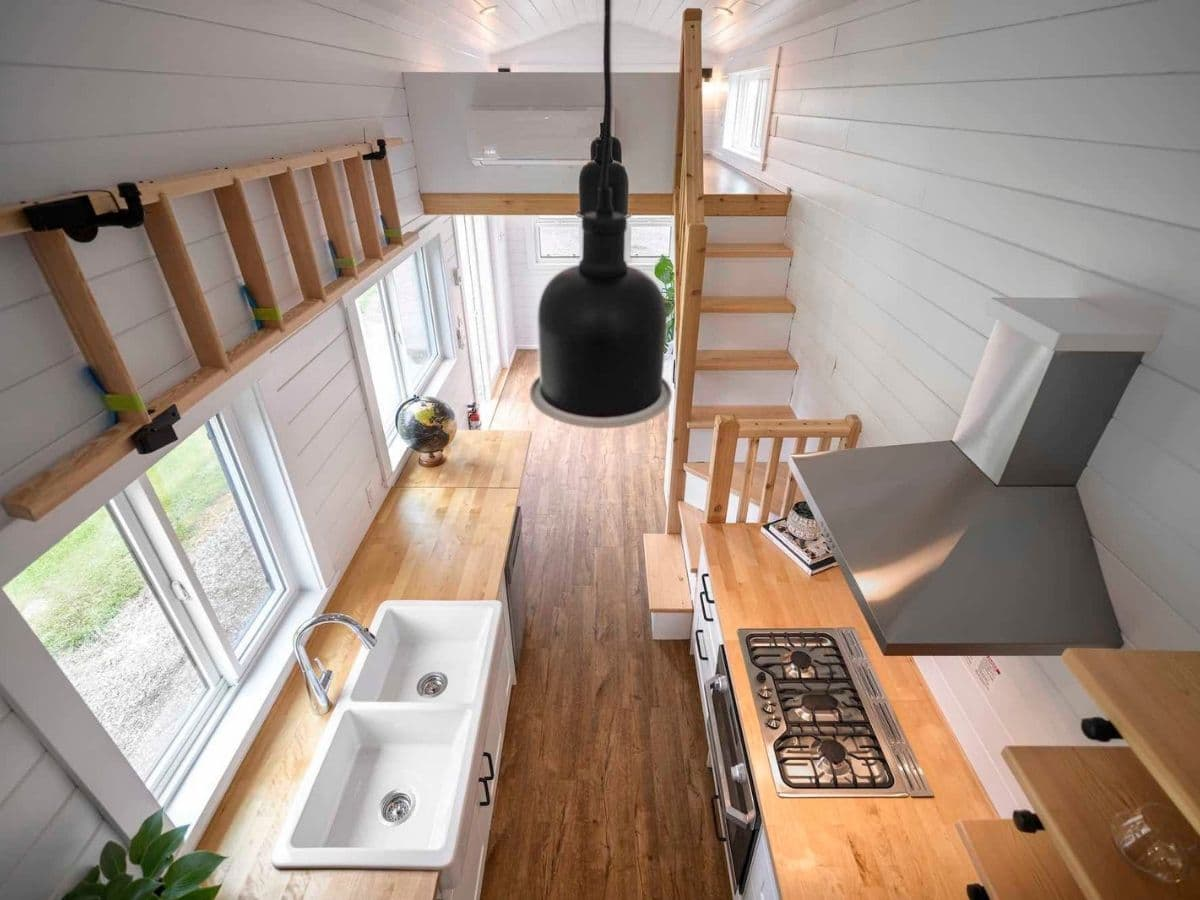 View across tiny home showing ladder on wall above windows