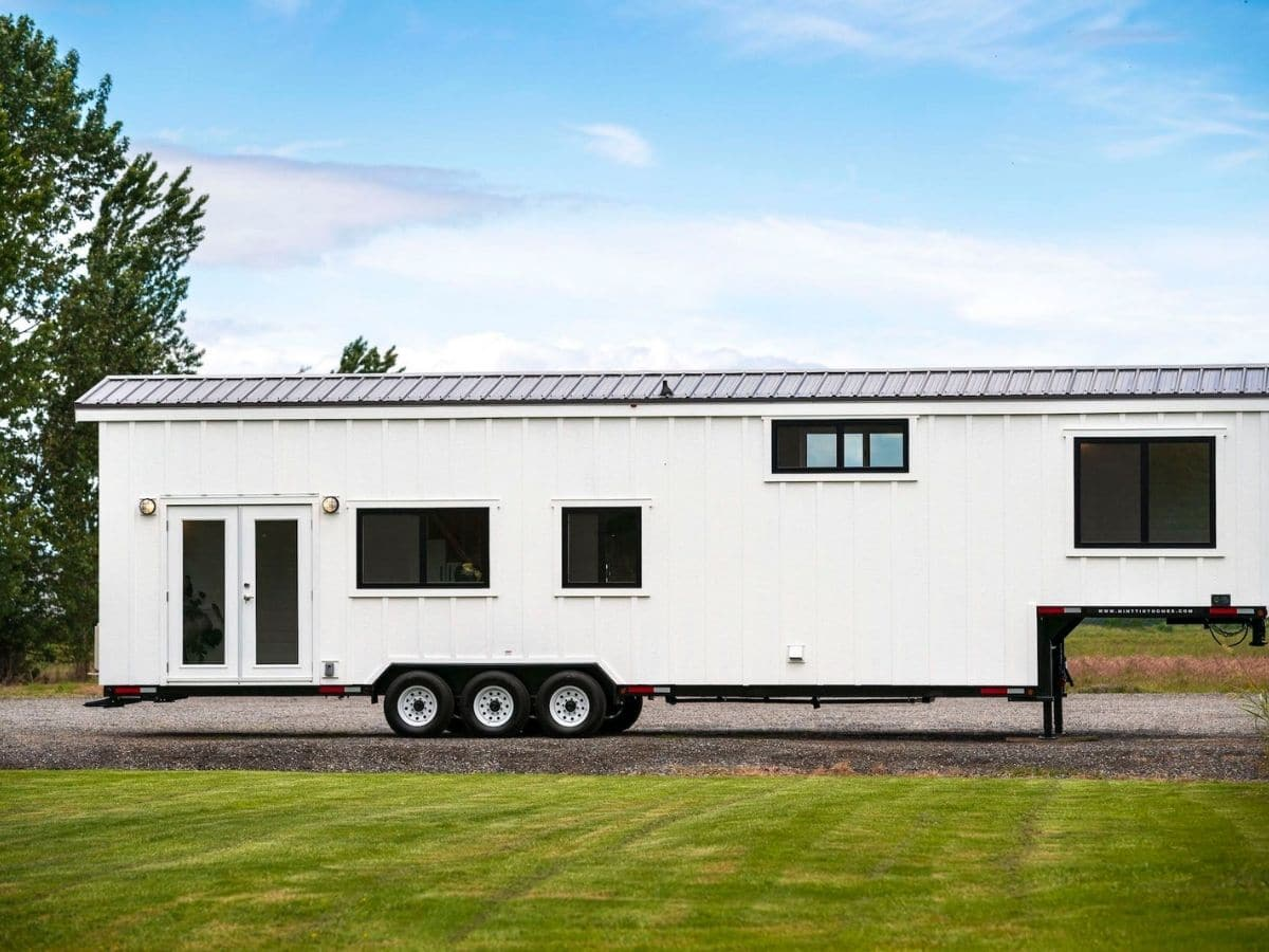 White tiny home on wheels with french doors on end