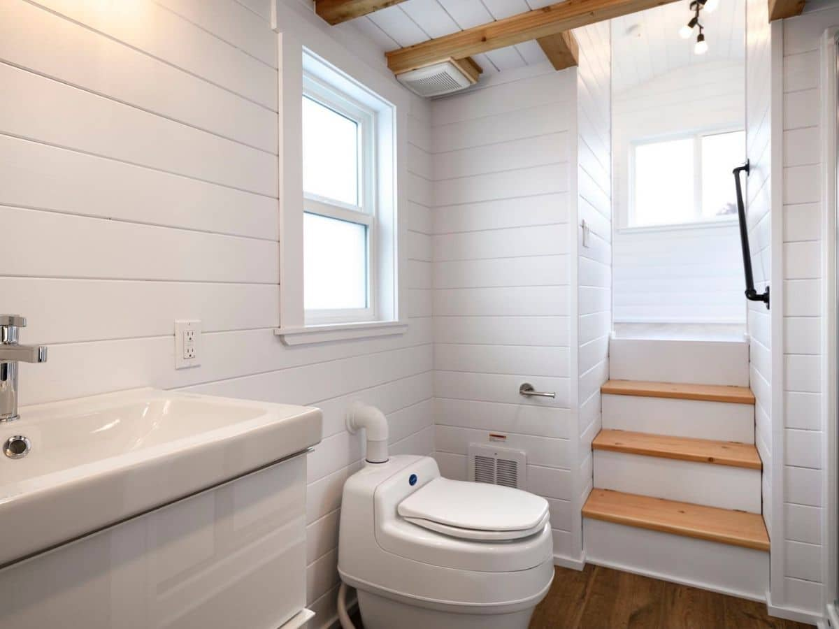 Composting toilet against wall next to stairs to loft