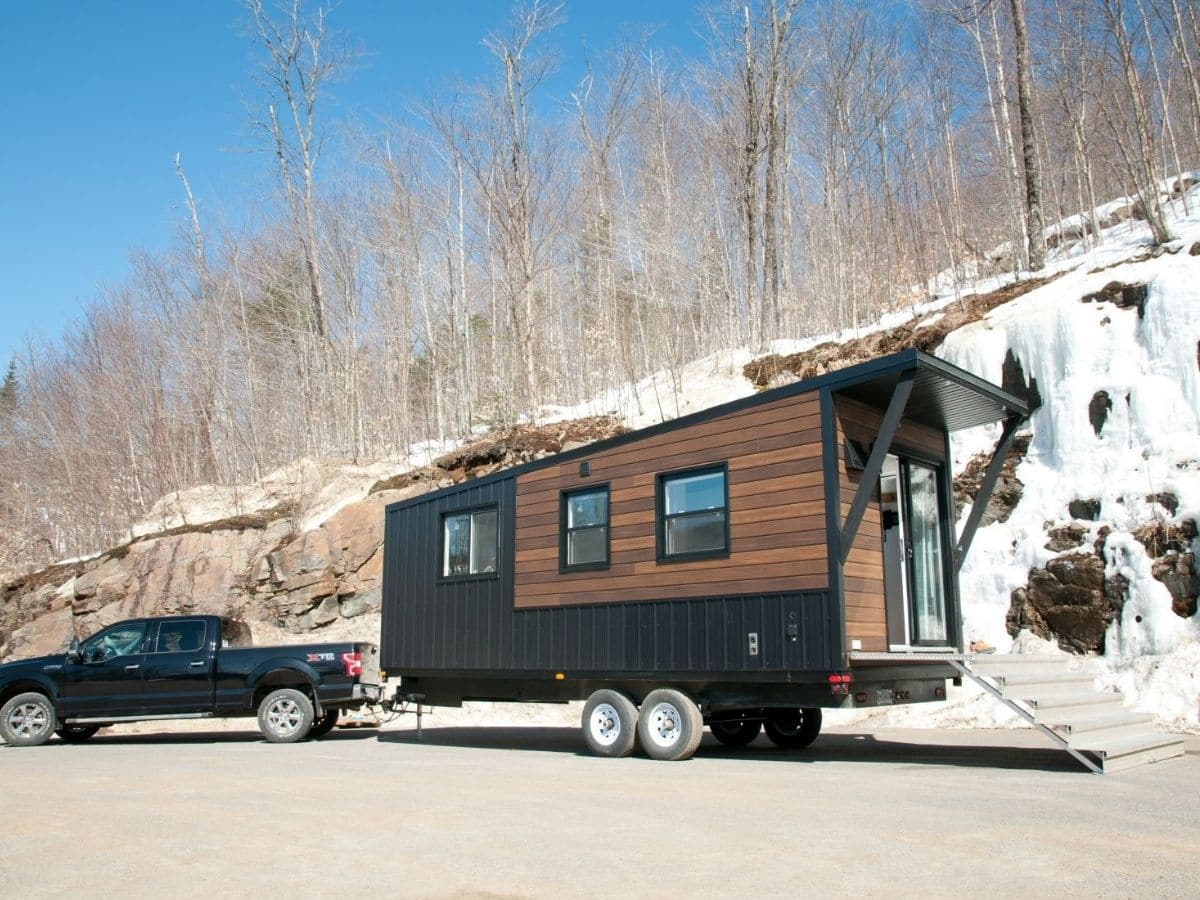 Black and wood tiny home behind black truck