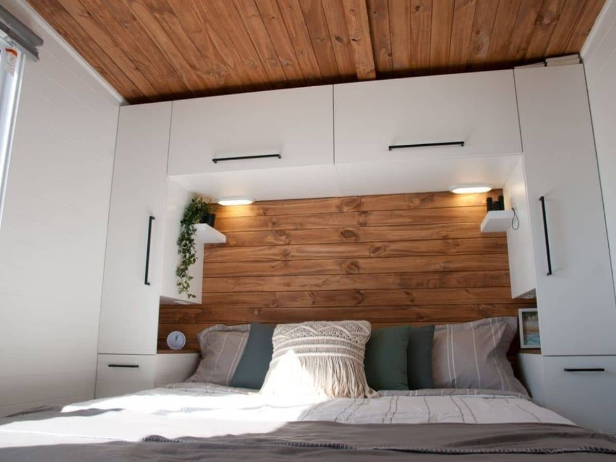 bed against wood wall with white cabinets above and on sides
