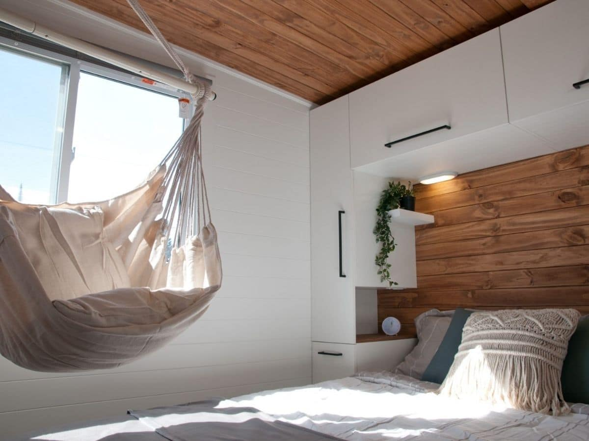 tan hammock hanging above bed by window from wood ceiling