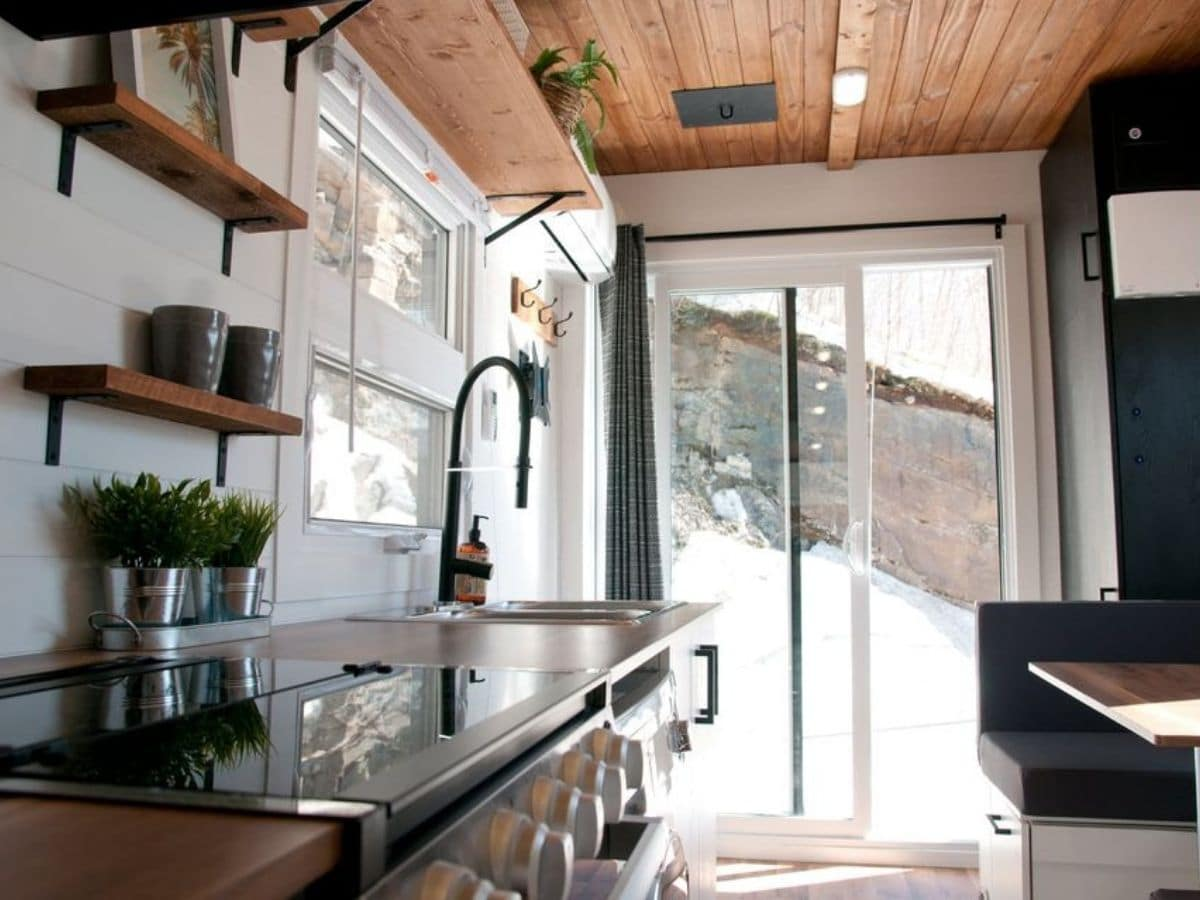 view from end of kitchen toward sliding glass doors at end of tiny home
