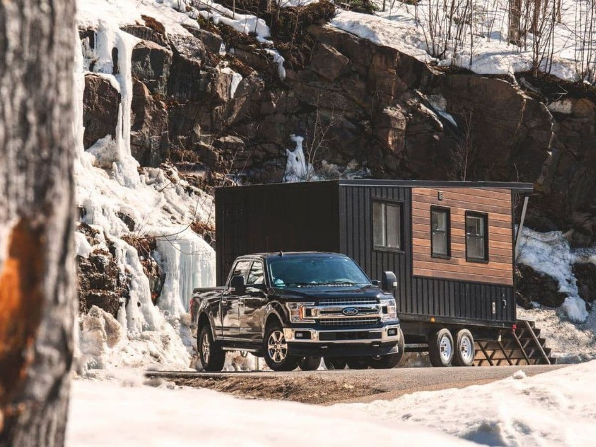 black truck pulling black and wood grain tiny home in front of snowy mountain