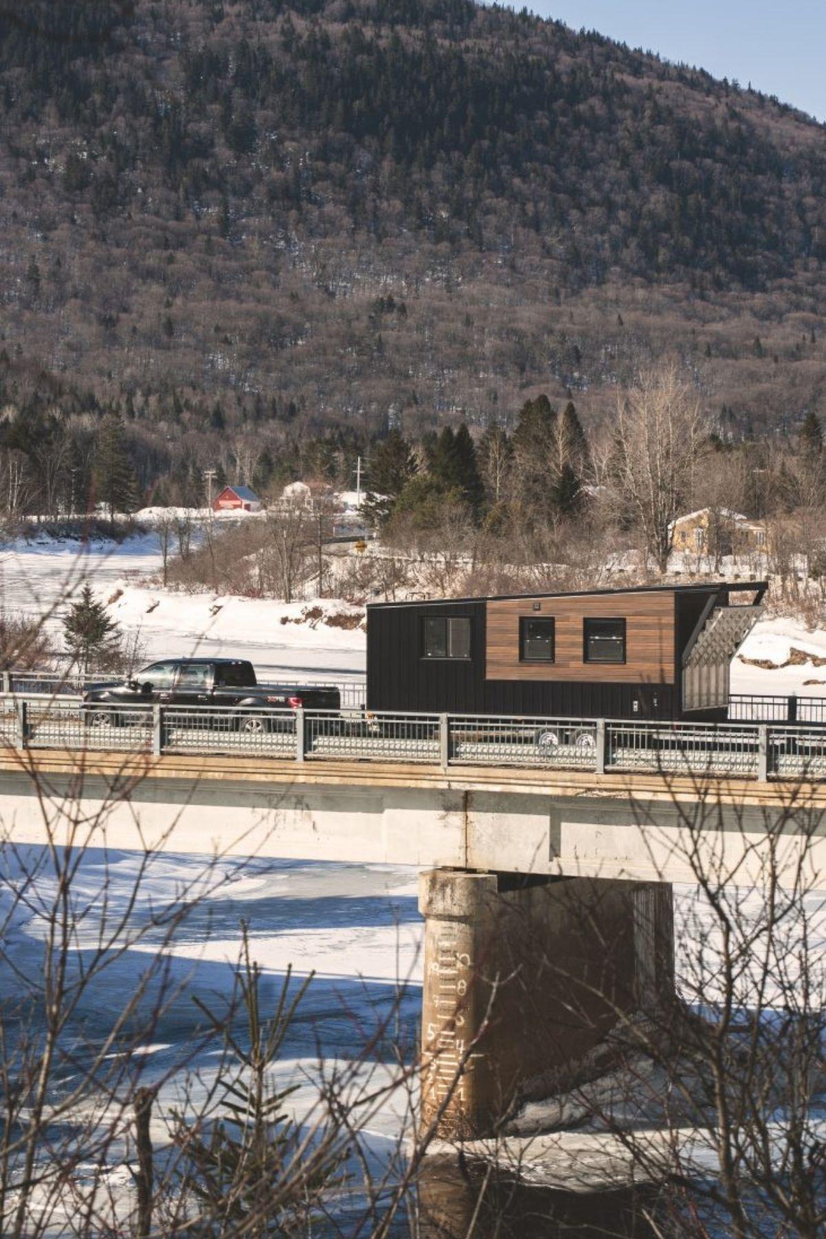 Black truck pulling wood tiny house across bridge