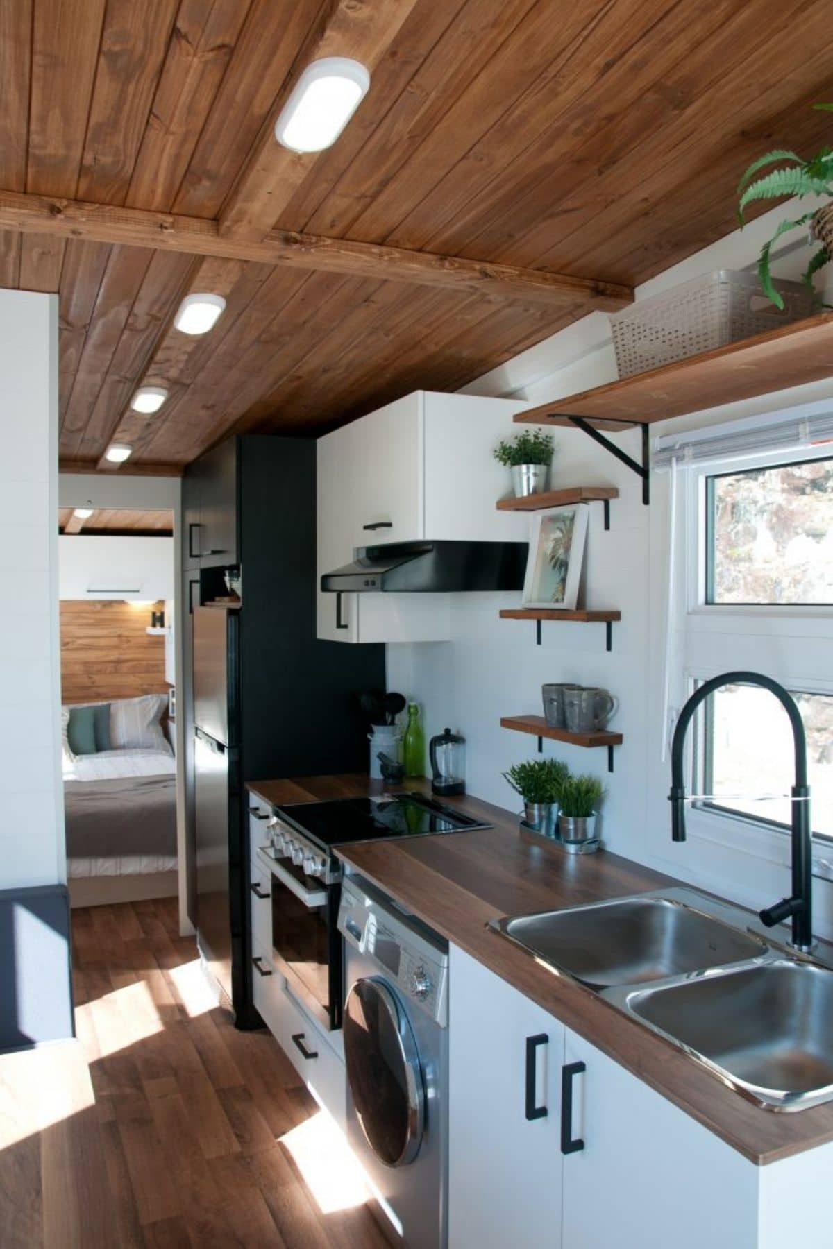 butcher block counter tops with deep stainless steel sink over white cabinets in kitchen