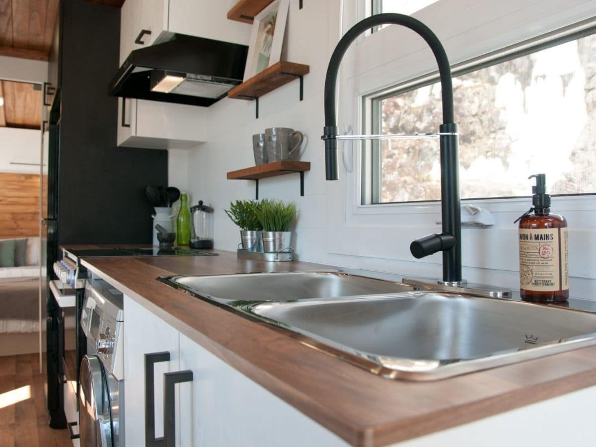 deep stainless steel sink in butcher block counter with black matte faucet
