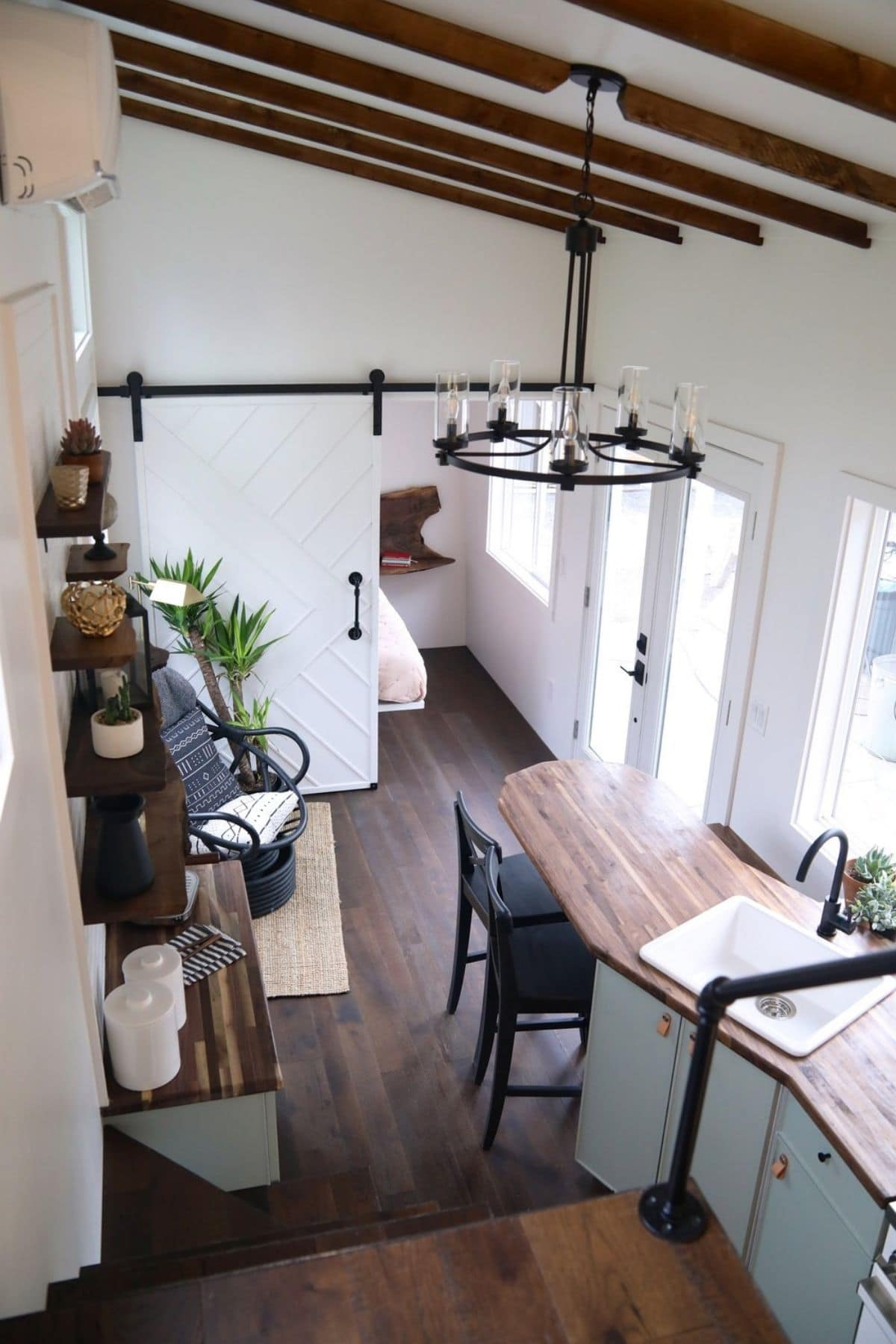 View from loft into tiny house living room and kitchen