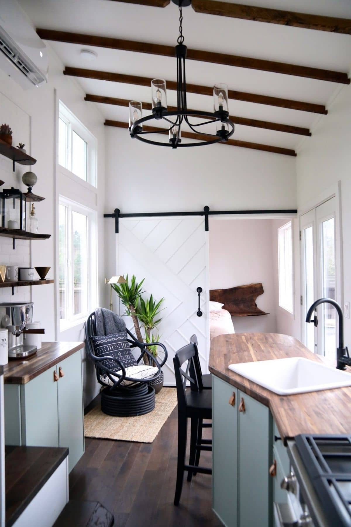 White kitchne sink at angle in foregruond with barn door to room in background