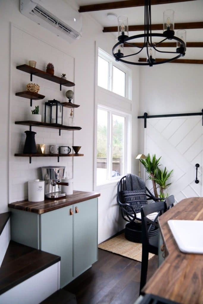 Floating shelves above small light green cabinet across from kitchen counter