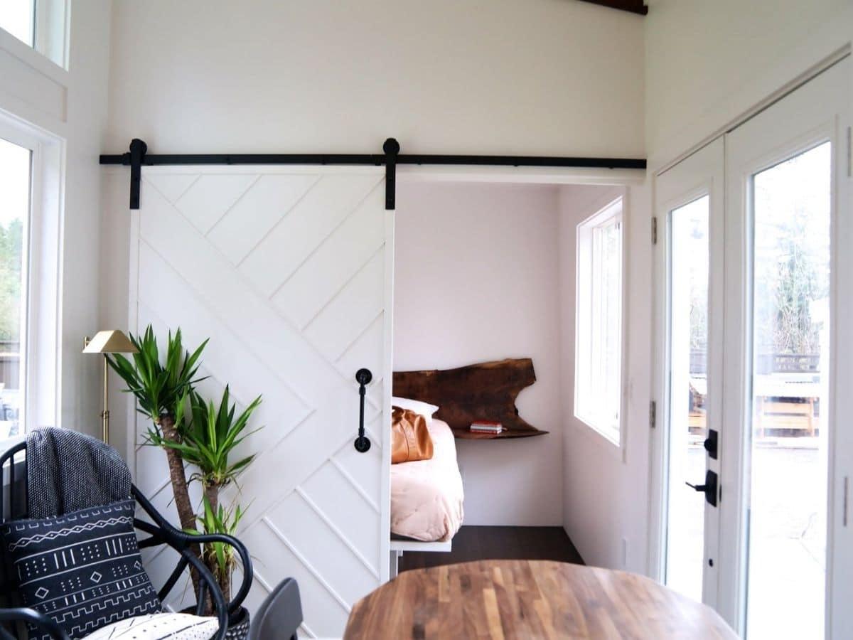 Open white barn door leading to bedroom across from front door
