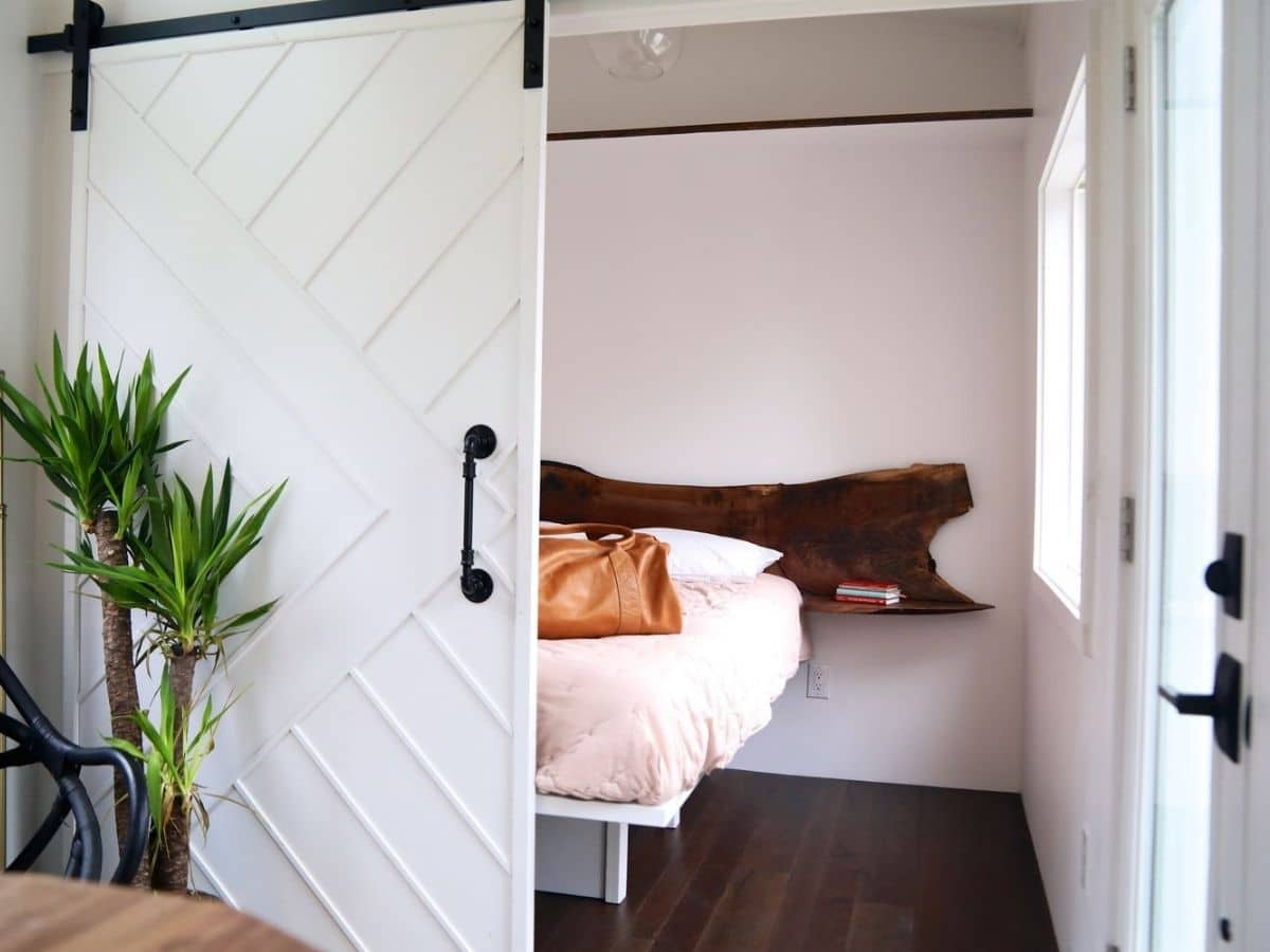 View into bedroom showing platform bed with wooden headboard