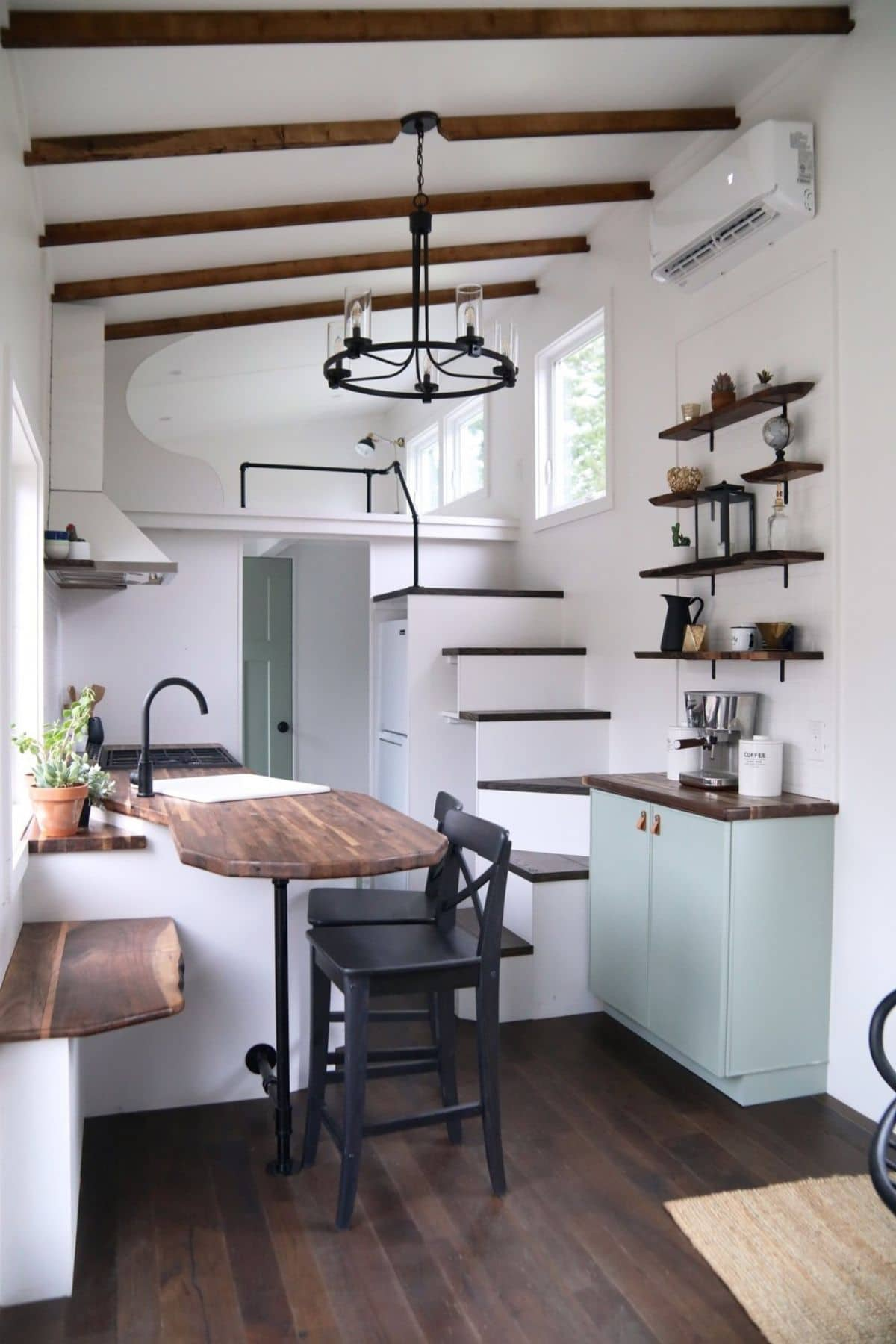 View into kitchen with black chairs at counter