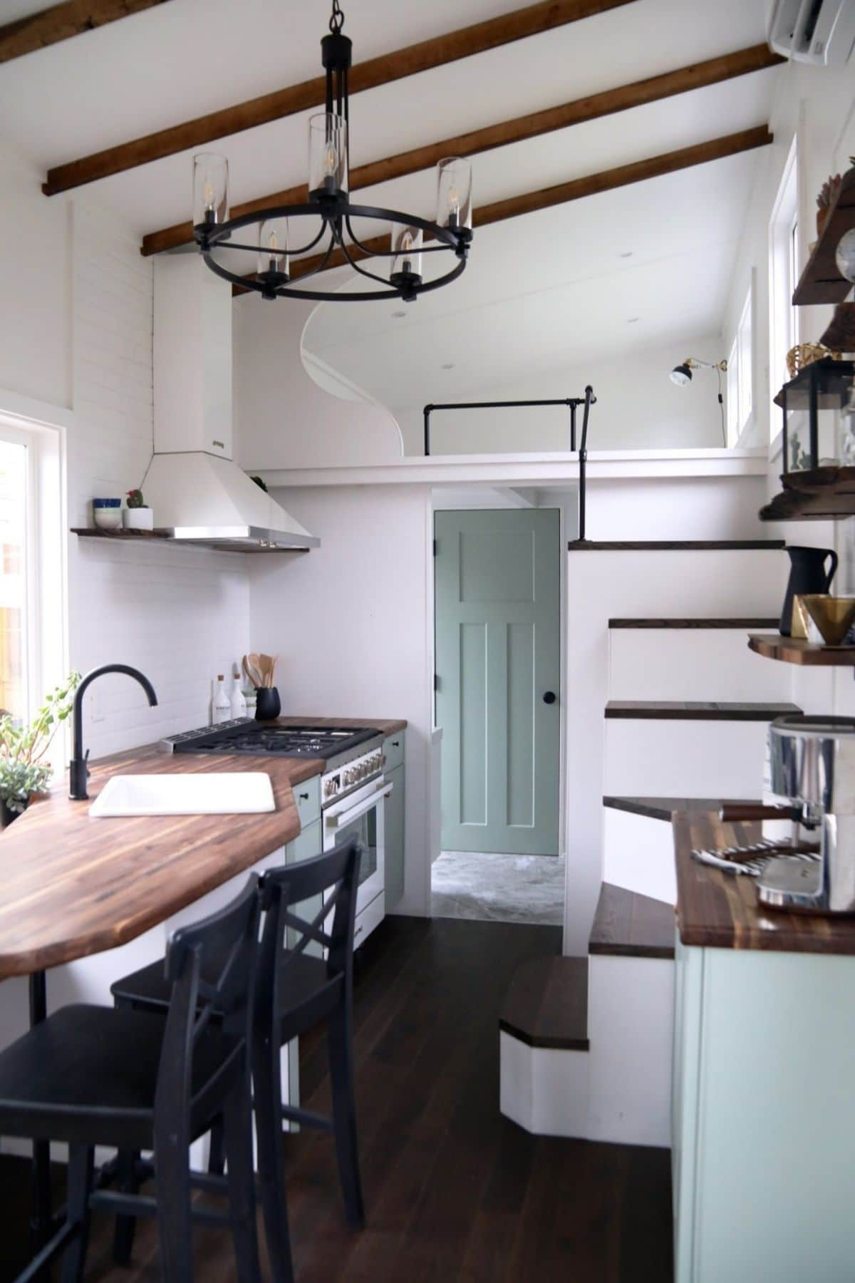 Wooden countertop with white and green cabinets in kitchen
