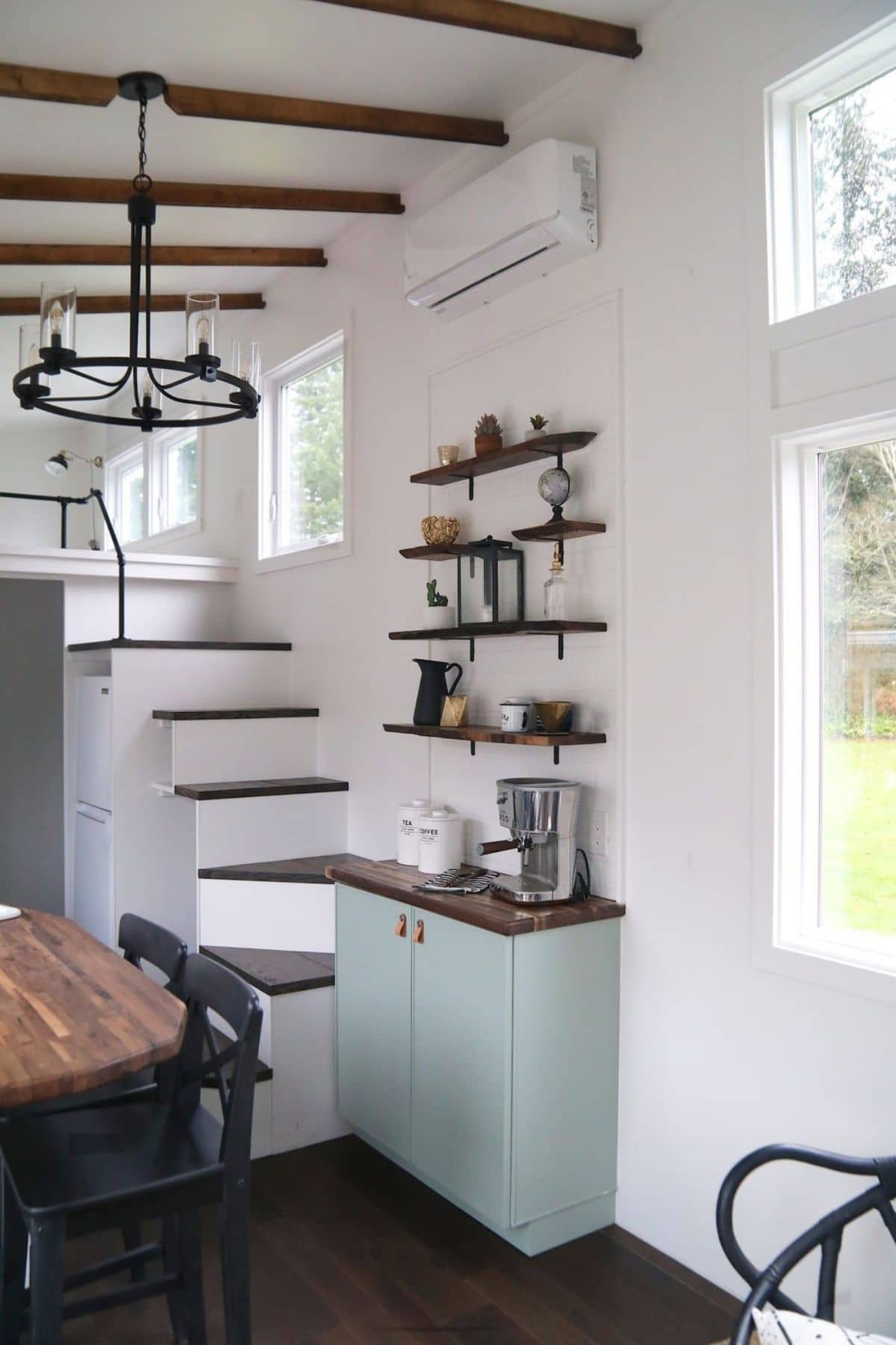 Light green cabinet at bottom of white stairs to loft