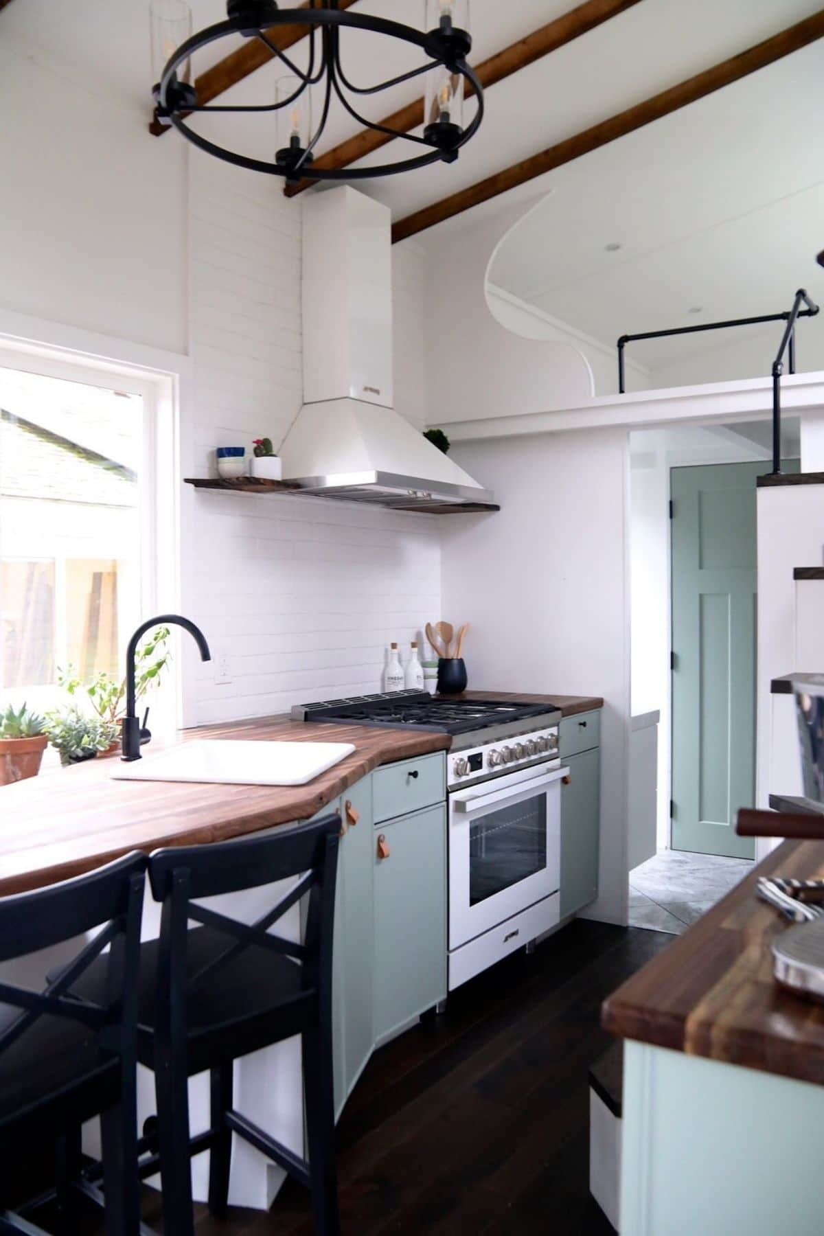 White full-sized stove in between light green cabinets in tiny home