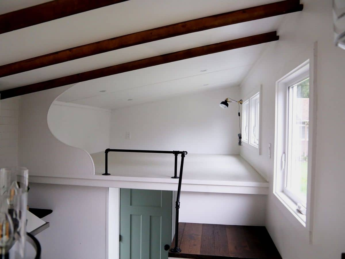 Loft with white floors and walls and black metal railing