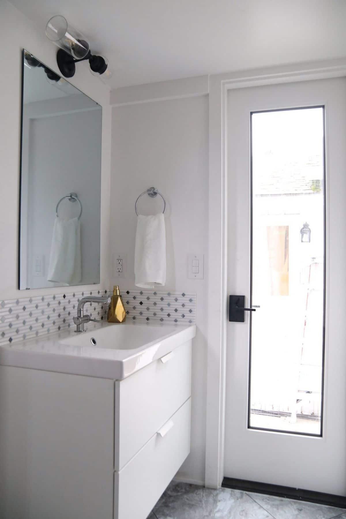 Tiled backsplash behind large white sink with gold faucet