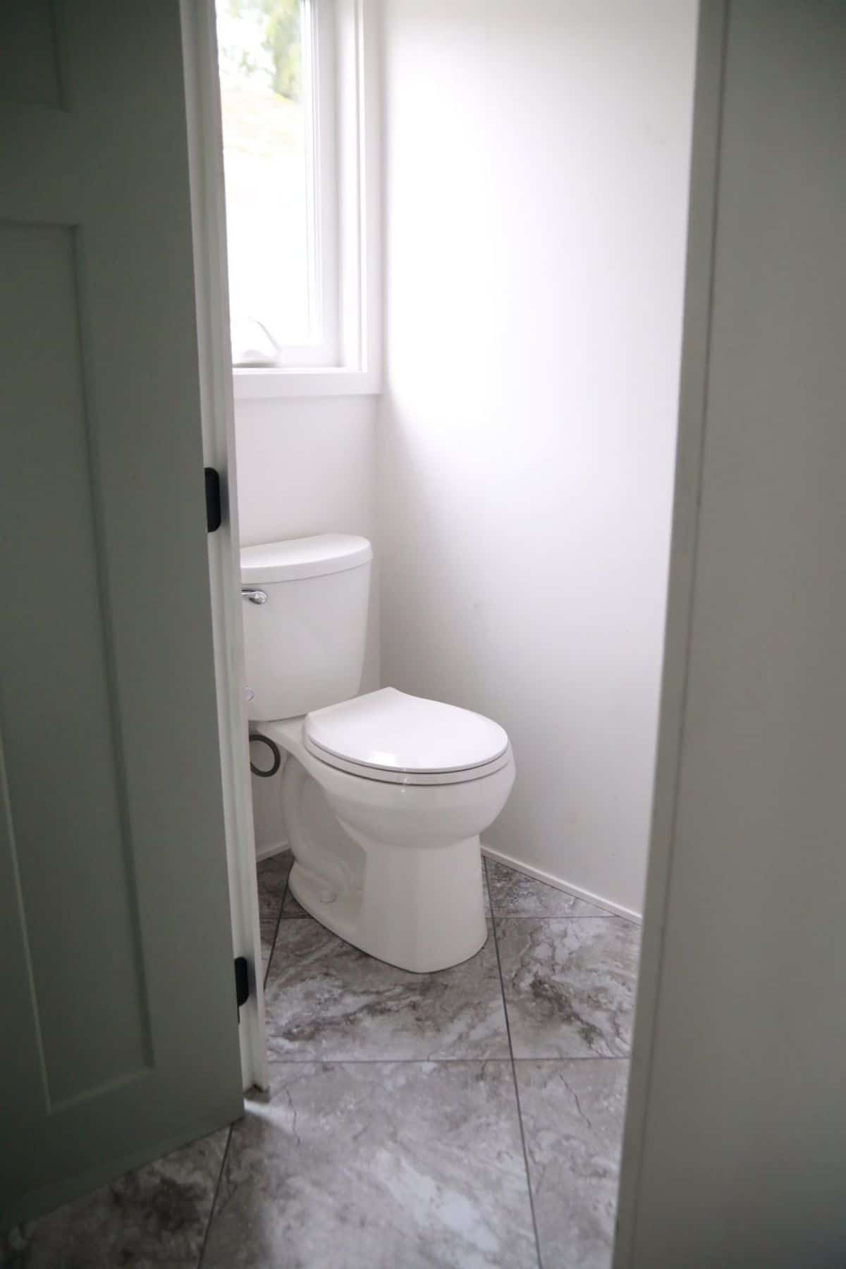 White flush toilet in white bathroom with marbled tile floor