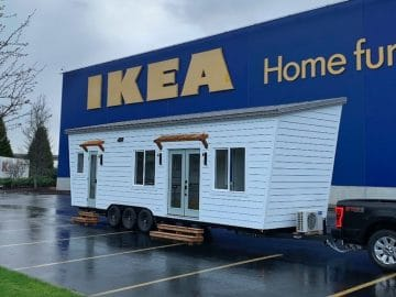White tiny home with truck in Ikea parking lot