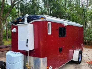 Red utility trailer with water tank on outside