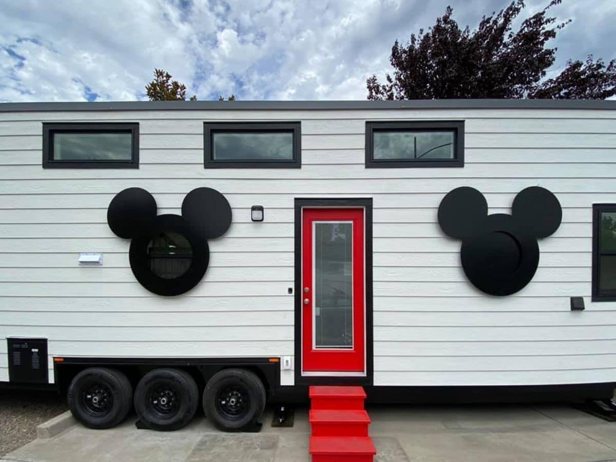 White tiny home with mickey mouse windows