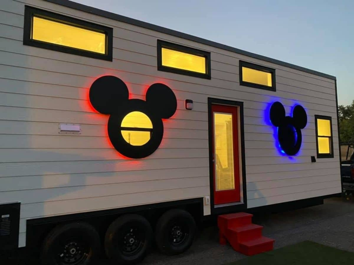 Tiny house with mickey and minnie windows lit after dark