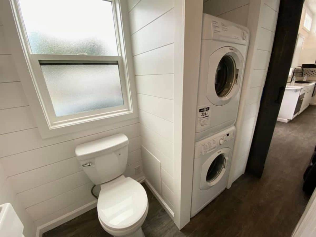 White bathroom with stacking washer and dryer next to toilet