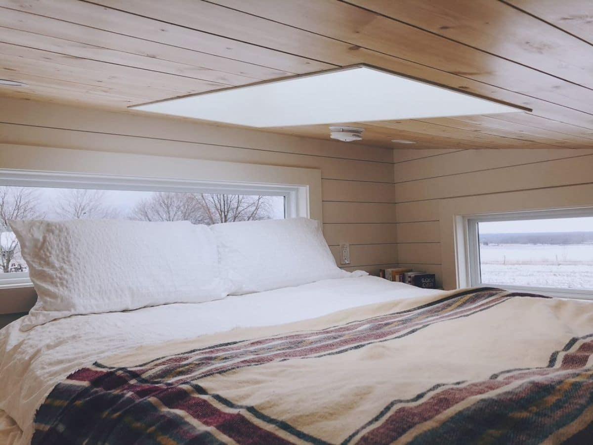 Bed in loft under skylight next to windows
