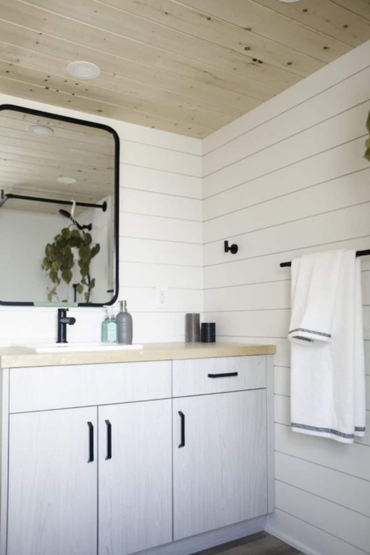 Bathroom with white shiplap walls and white vanity beneath mirror with black trim