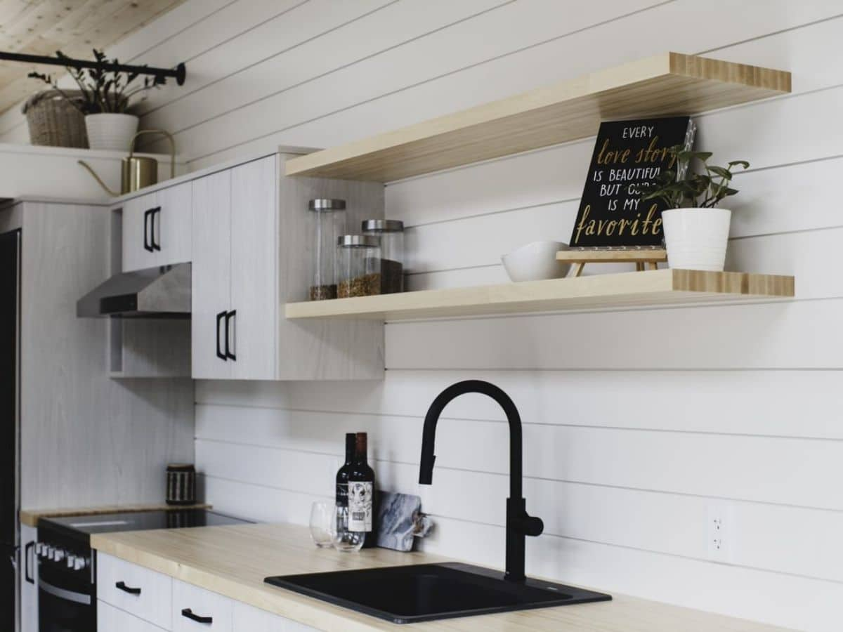 White shiplap wall behind black sink and white cabinets