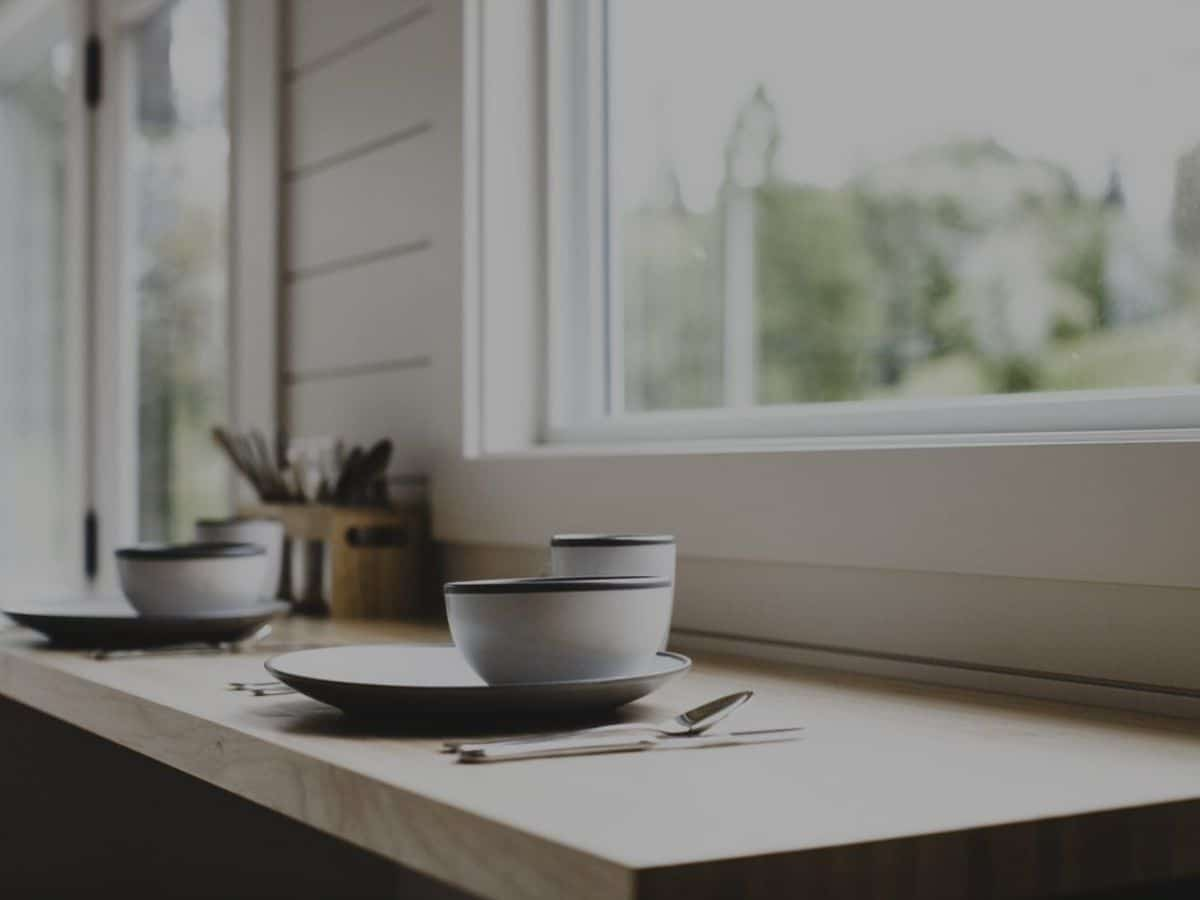 Table under window with bowl on plate
