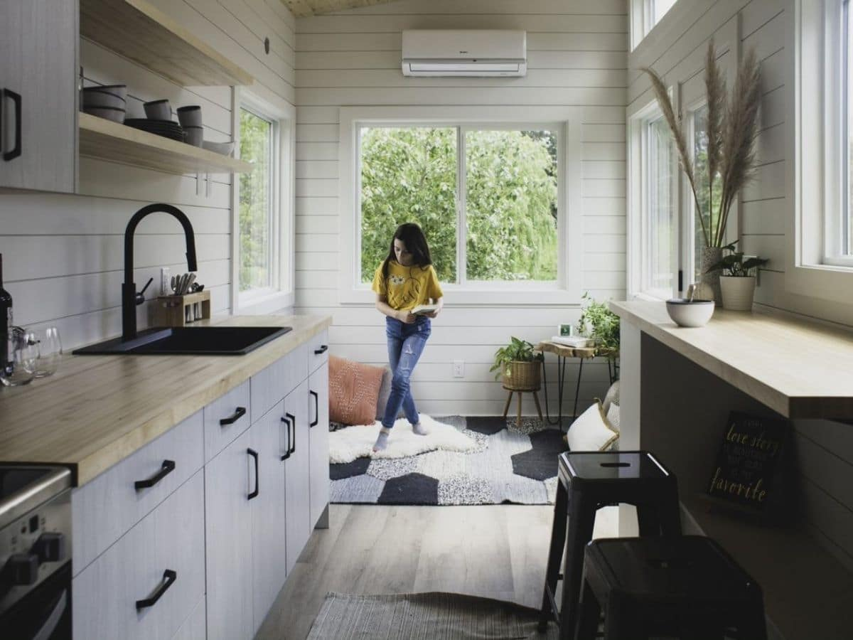 Girl standing on rug in front of window at end of living room