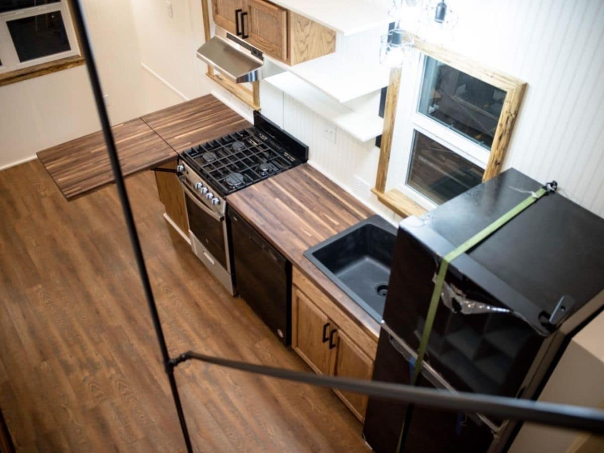 view from stairs down into kitchen showing wood floors and counters