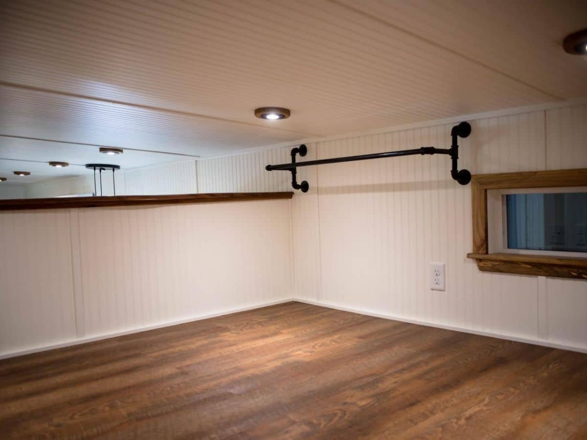 black closet bar against white wall of tiny home loft