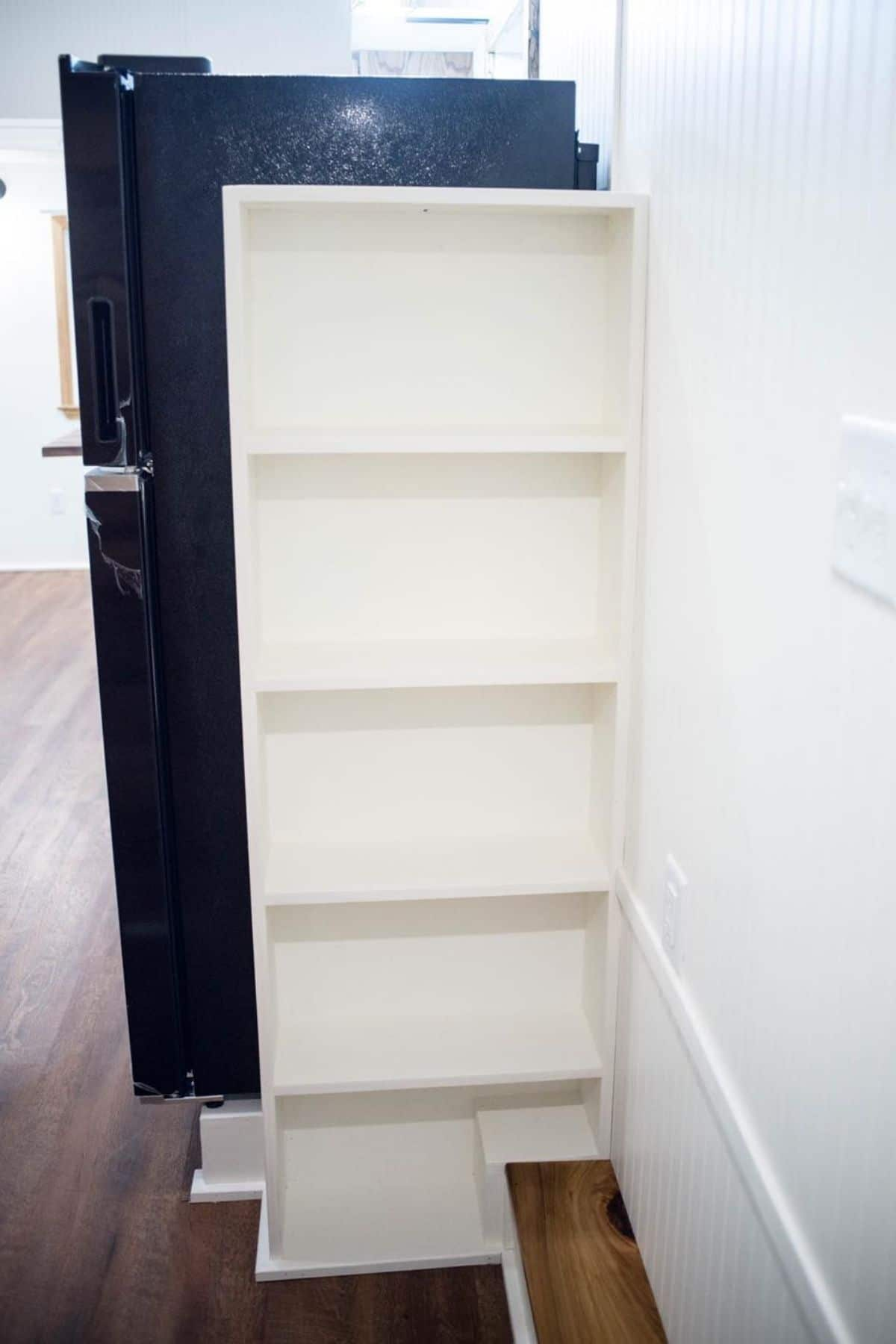white shelf beside black refrigerator